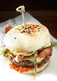 "Shojo's take on the burger, ""The Shojonator,"" is a 4-ounce patty on a steamed bao, with bacon and ""kimcheese."""